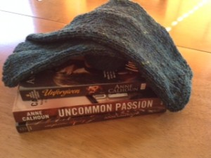 A stack of books from Anne Calhoun with arm warmers resting on top.