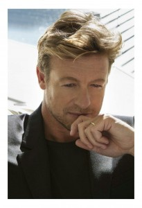 Simon Baker with one hand against his lip, looking down away from the viewer - and also looking kinda hot, too