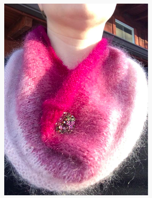 Elyse's pink fluffy cowl with a big sparkly button on it