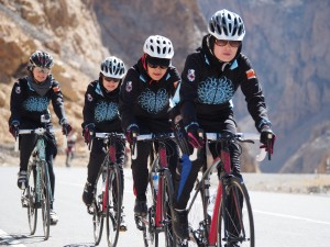 Women on cycling team biking up hill in Afghanistan. Their jackets have a light blue pattern on the chest, almost like a sun