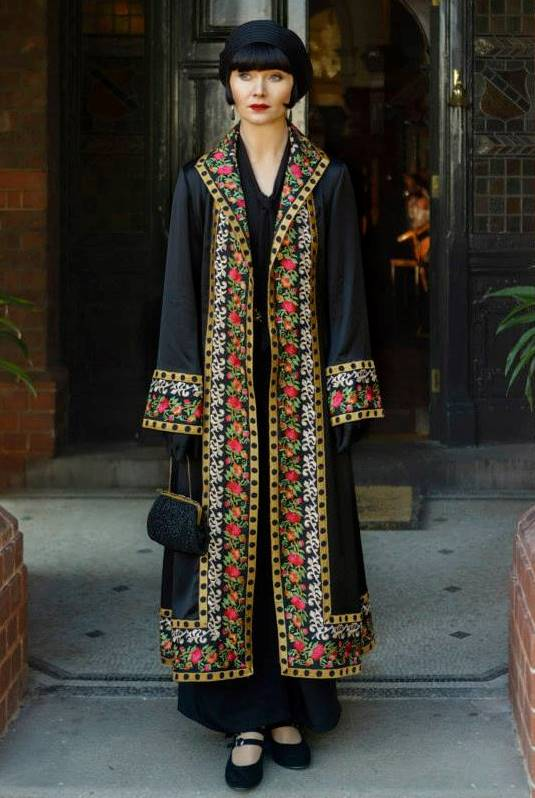 bafc13f76742b4 Phryne in a long coat embroidered with a colorful pattern on the lapel, hem  and