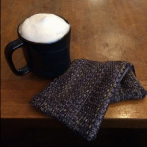 Cowl sitting on wood table next to cappucino
