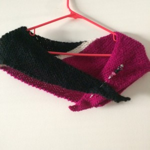 magenta and black shawl over a hangar with a pin holding it shut