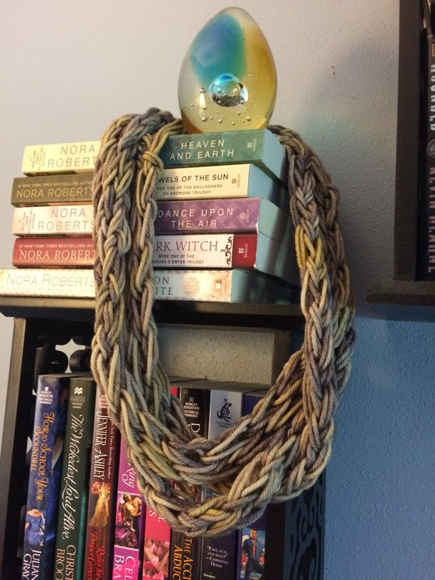 A braided loop of three fingerknit strands in a three-strand necklace of sorts, draped over a paperweight on top of some books.
