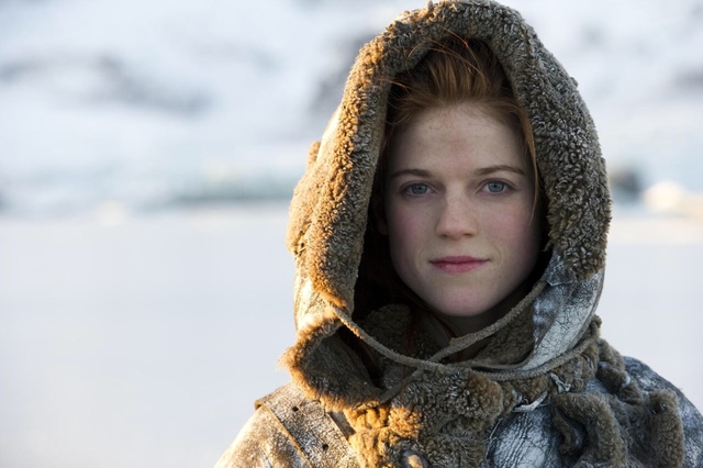 Ygritte, who has red hair and beautiful grey eyes, in a hood in the snow looking at the camera