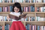 A little girl with glasses and a red skirt reading a big book in the library