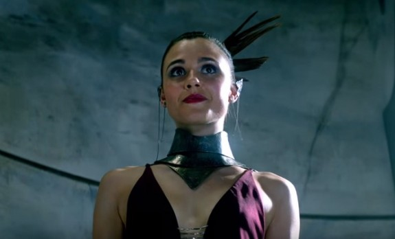 Close up of one of the characters in a tight purple dress with cutaways over her inner breasts and sternum, plus a black leather collar with a deep vee in the front to set off the plunging neckline of the purple dress, and then there's really thick shiny makeup and some kind of scraped back hairstyle with feathers in the back or something I don't even know