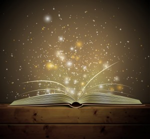 Open book with light and sparkles floating up from the pages.