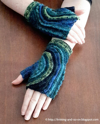 Blue swirl fingerless gloves with a starry-night kind of sky pattern with blue and green thick swirls crossing the back of the hand