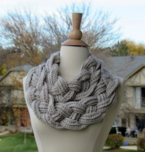 Braided cowl in grey with two looping fat braids over the neck of a mannequin form
