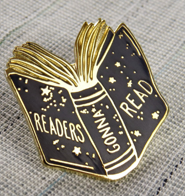 Black enamel pin of an open book with Readers Gonna Read written across the cover and spine