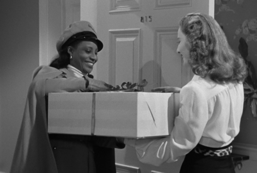 A black deliverywoman wearing a cape and hat, delivering a large box!