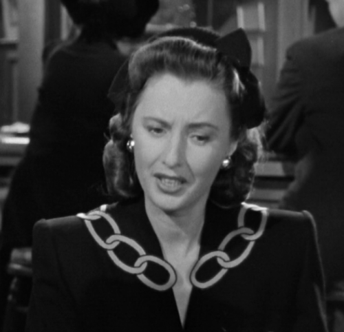 Elizabeth's dark-colored dress with chain-looking trim on the collar.