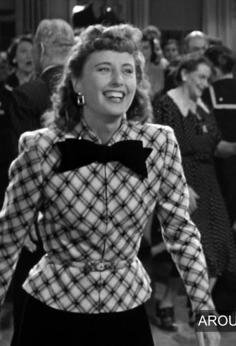 A plaid-esque jacket with a large black bow tie.