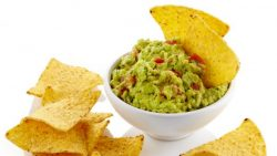 A bowl of guacamole with tortilla chips.