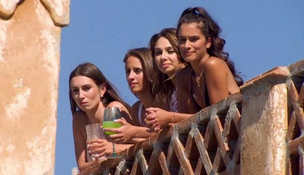 Vanessa cradles a wine glass of Mountain Dew while she and three other women look at the bouncy castle.
