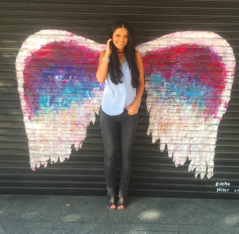 Raven stands in front of street art of angel wings, making her look like she's got wings