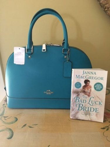 A blue Coach purse with a copy of The Bad Luck Bride