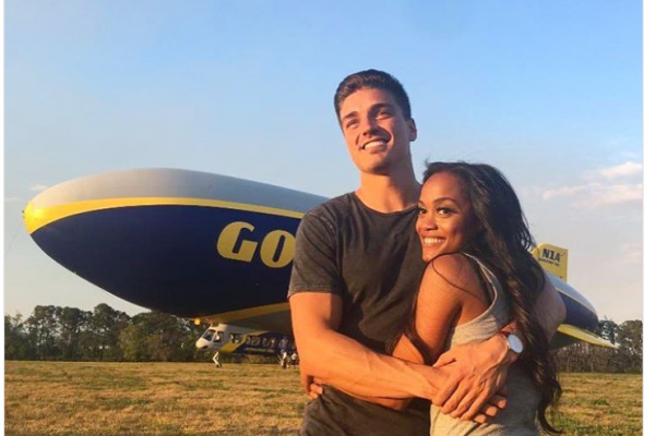 Dean and Rachel hug in front of the Goodyear blimp