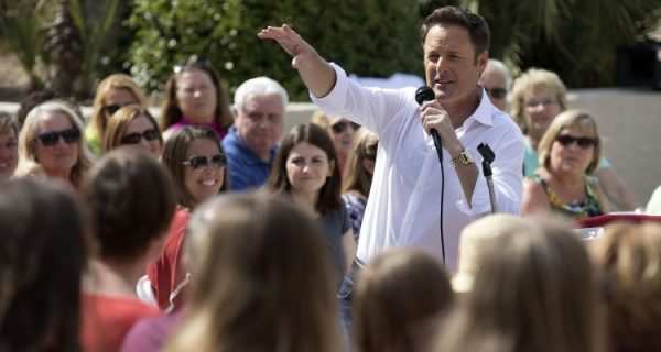 Chris Harrison stands in the middle of a crowd, talking into a mic.