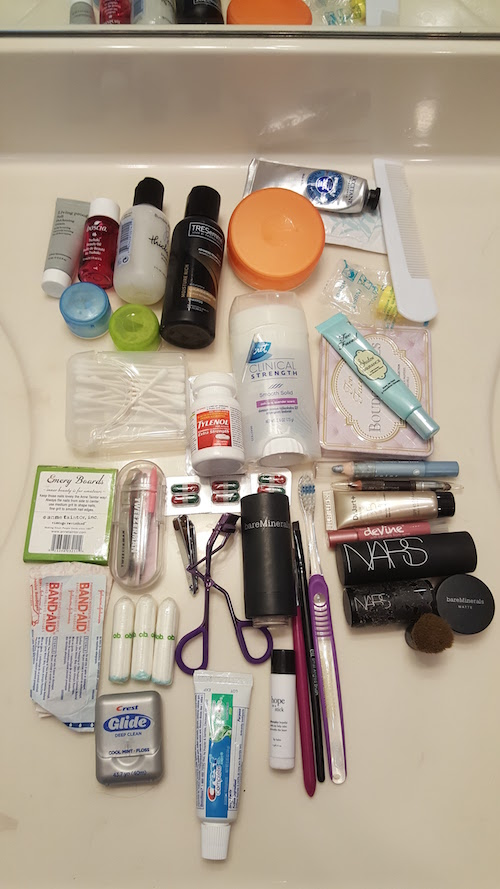 All my travel toiletries on the counter, including shampoo, toothbrush, makeup, etc.