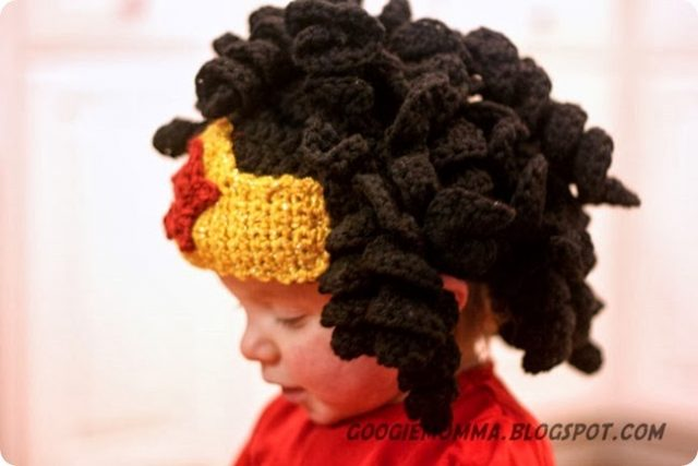 A super adorable baby wears a hat that is crocheted to look like Wonder Woman's headband with her long black curls flowing out from over it.