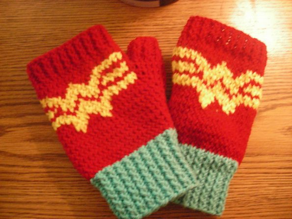 A pair of red fingerless gloves with the Wonder Woman logo across the back of the hands.
