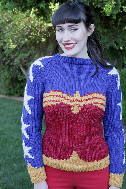 A woman models a pullover sweater designed to look like Wonder Woman's bodice against a blue backdrop with stars.