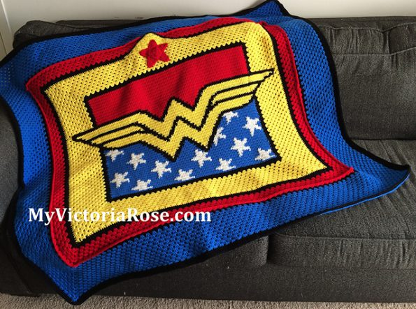 A throw blanket draped across a sofa. The Wonder Woman logo is in the center, with red above and white stars on a blue field below. There are red and blue borders.
