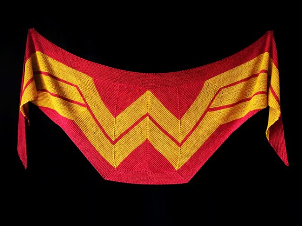 A modified triangular shawl with a red background and the Wonder Woman logo in gold.