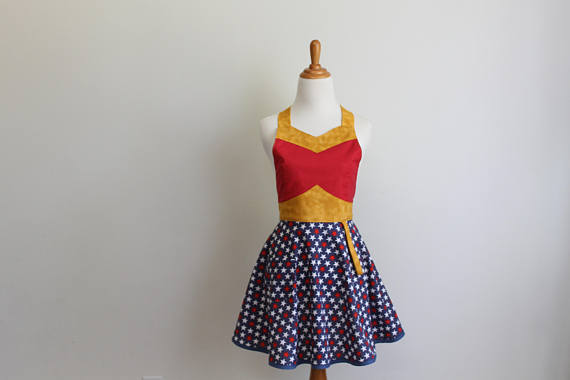 An apron on a dress form. The skirt is blue with stars and the bodice is red. There is gold trim along the bust and waist.