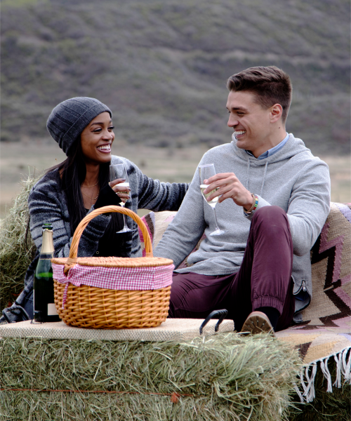 Dean and Rachel sit on hay bales and enjoy a picnic.