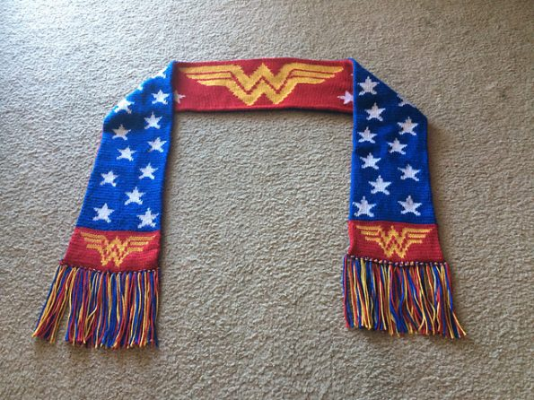 A long scarf with tassled ends. On one side is the Wonder Woman logo against a red backdrop. The other side is blue with white stars.