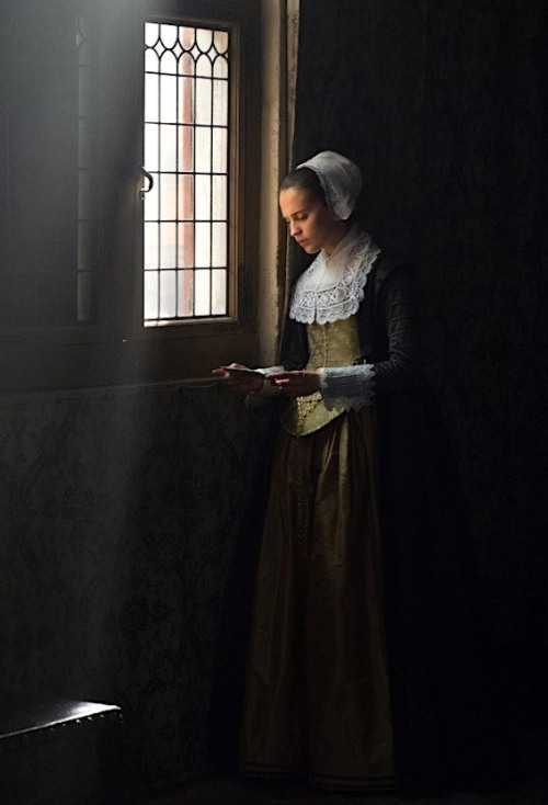 Alicia Vikander, next to a window with a letter. The shot is composed like a Vermeer painting with light streaming in.