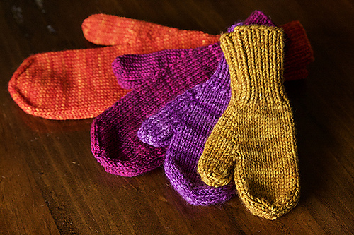 Four mittens in different sizes and colors are displayed on a wooden table.