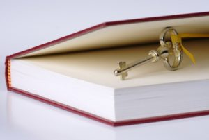 A gold key perched between the cover and first page of a book.