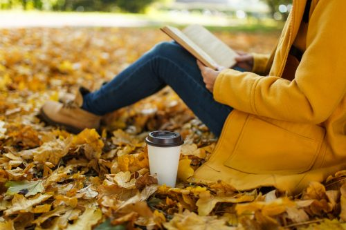 The woman in yellow coat jeans and boots sitting under the maple tree with a red book and cup of coffee or tea in fall city park on a warm day. Autumn golden leaves. Reading concept. Close up.