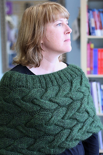A woman wears a green cabled shrug that wraps around the upper portion of her body like a big cowl.