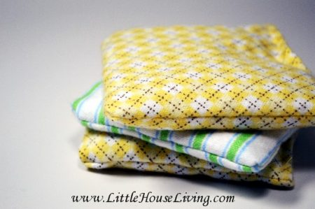 Three handwarmers stacked on each other. Two have a yellow check pattern and one is blue and white striped.