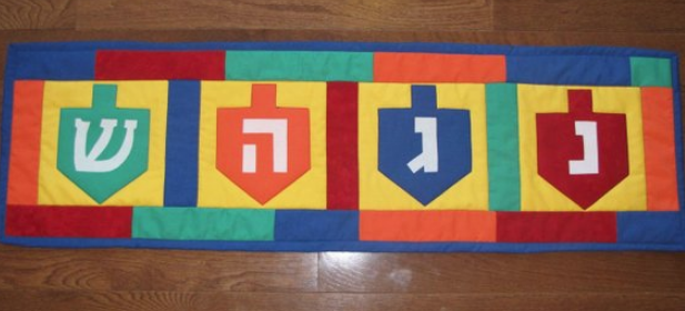 Hanukkah Dreidel table runner in green blue orange an red with four dreidels across the top
