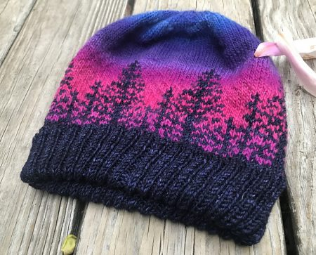 Another version of the Alaska hat with a dark blue brim and trees and a pink and violet background.