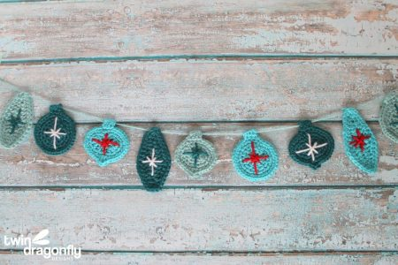 A garland of crocheted Christmas ornaments in teals with red and white accents.