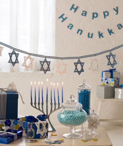 A garland of the Star of David crocheted in white and blue is hung over a table set with a menorah, gifts and candies.