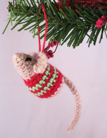 A tiny mouse wearing a red and green sweater hangs from a Christmas tree. And OMG is it cute.