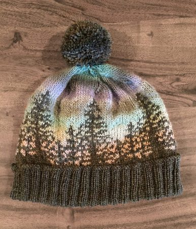 A beanie style hat that has a brown brim with the outline of fir trees in the same brown. The background is made with an ombre yarn so it looks like the trees are silhouetted against a sunset.