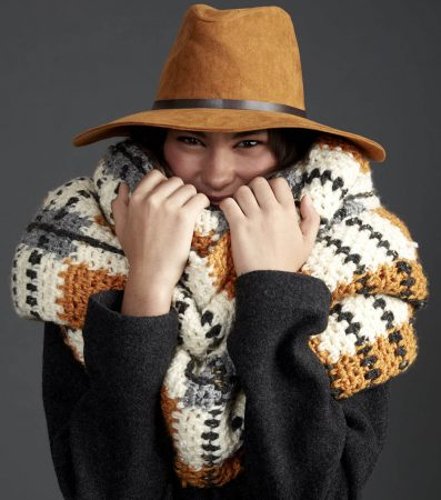 A woman in a super cute hat is all snuggled up in a giant tartan scarf. The main color is cream with contrasting stripes of brown, black and gray