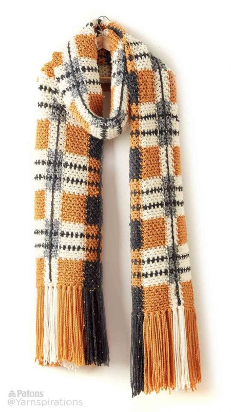 Another view of the tartan scarf. This time its draped over a hanger against a white background.