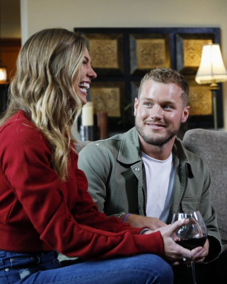 Hannah B laughs as she holds a glass of wine. Colton smiles at her.