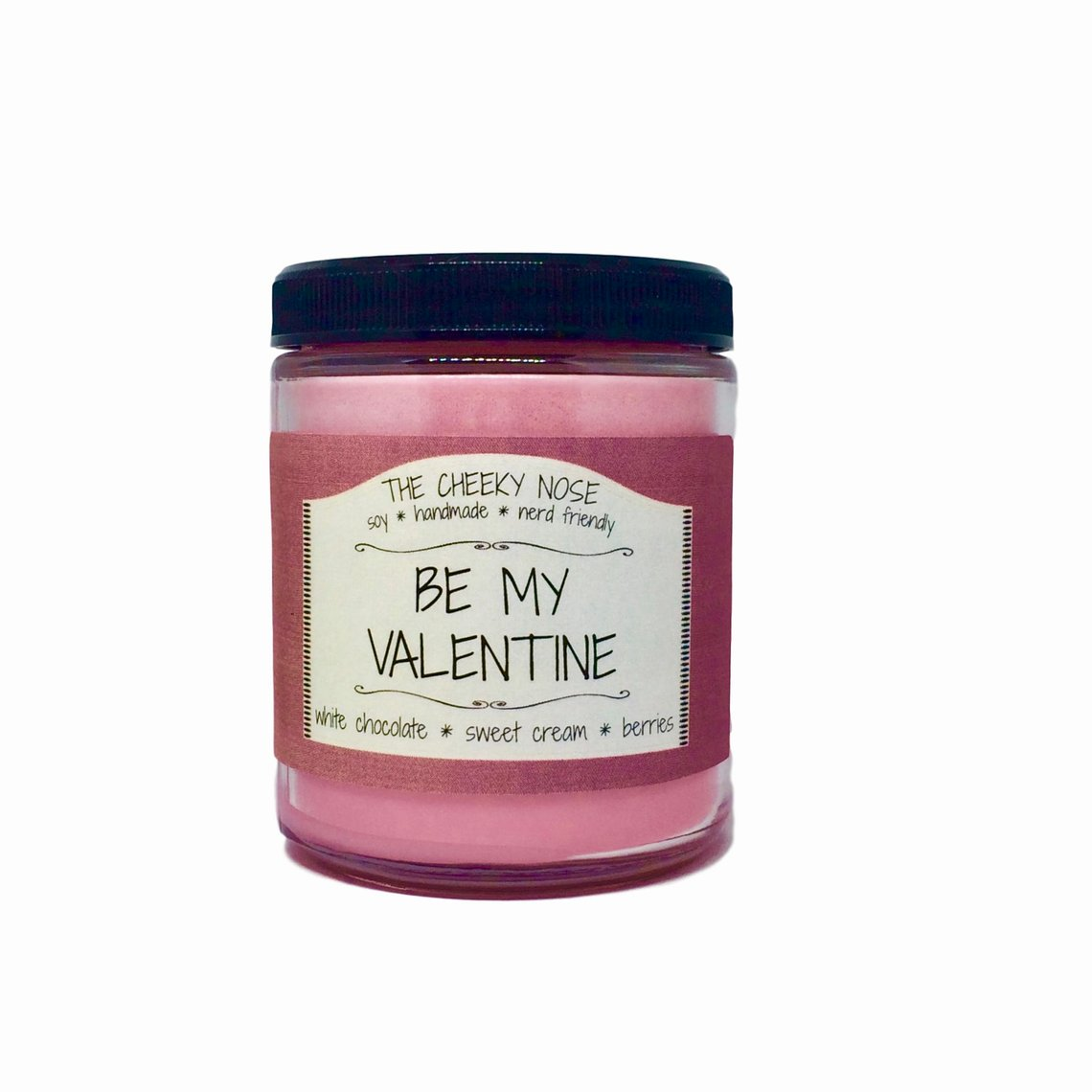 A bright pink candle in a glass jar with a raspberry colored label