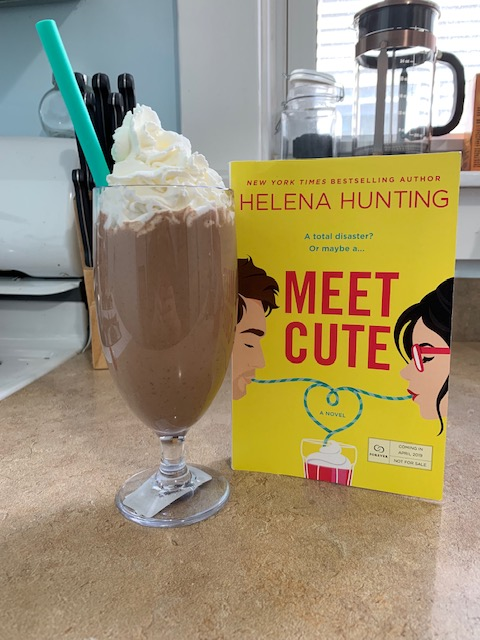 A chocolate peanut butter milkshake next to a copy of Meet Cute by Helena Hunting